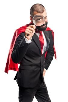 Super held zakenman met vergrootglas