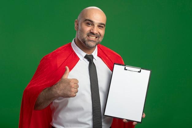 Super heldzakenman die in rode cape klembord met blanco pagina's tonen die voorzijde het glimlachen bekijken die duimen tonen die zich over groene muur bevinden
