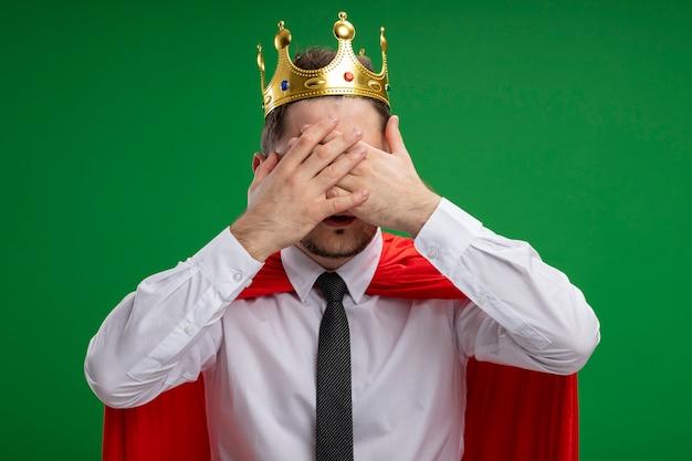 Super heldzakenman in rode cape die kroon draagt die ogen behandelt met handen die zich over groene achtergrond bevinden