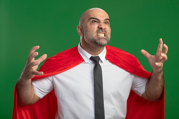 Super heldzakenman in rode cape die wild opheft handen met agressieve uitdrukking die zich over groene muur bevindt
