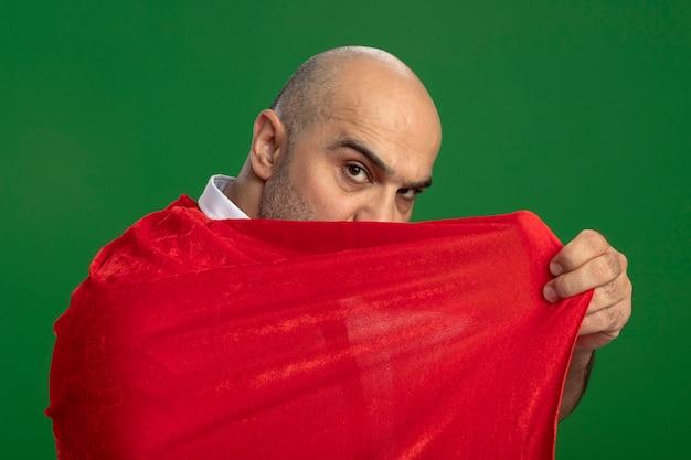 Super heldzakenman in rode cape die zijn gezicht behandelt die zich zelfverzekerd over groene muur bevinden