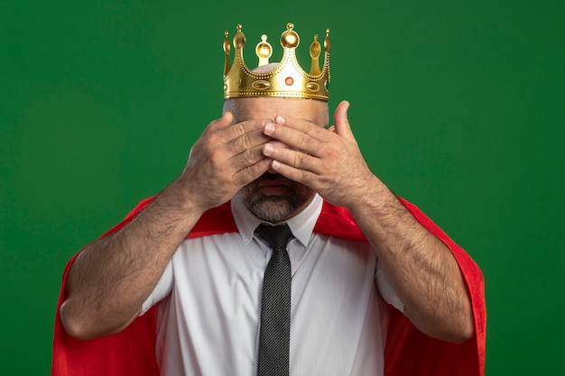 Super heldzakenman in rode cape en glazen die kroon dragen die ogen behandelen met handen die zich over groene muur bevinden