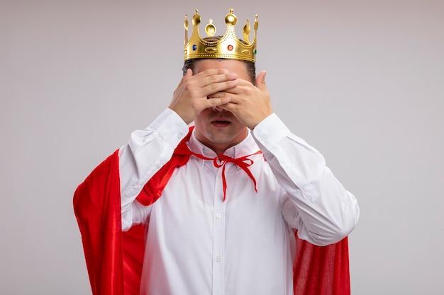 Super heldzakenman in rode cape en glazen die kroon dragen die ogen behandelen met handen die zich over witte muur bevinden