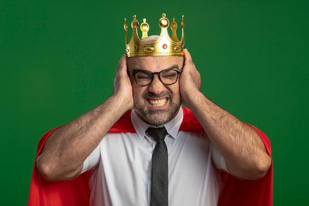 Super heldzakenman in rode cape en glazen die kroon dragen die tijdperken bedekken met handen met geïrriteerde uitdrukking die zich over groene muur bevindt