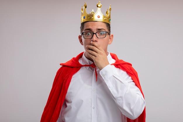 Super heldzakenman in rode cape en glazen die kroon dragen die verbaasd en verrast worden die mond behandelen met hand die zich over witte muur bevindt