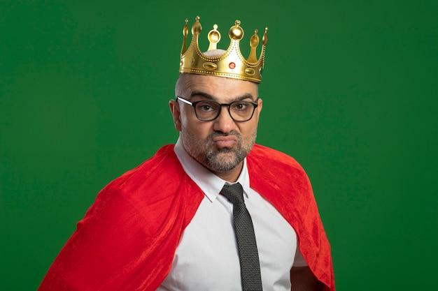 Super heldzakenman in rode cape en glazen die kroon dragen die voorzijde zelfvoldane status over groene muur bekijken