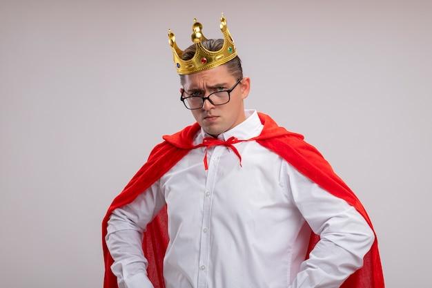 Super heldzakenman in rode cape en glazen die kroon met ernstig gezicht met wapens op heup dragen die zich over witte muur bevinden
