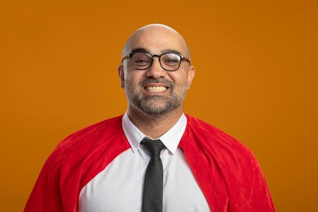 Super heldzakenman in rode cape en glazen die voorzijde glimlachend in grote lijnen gelukkig en positief status over oranje muur bekijken