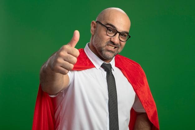 Super heldzakenman in rode cape en glazen die voorzijde glimlachend met gelukkig gezicht bekijken die duimen tonen die zich over groene muur bevinden