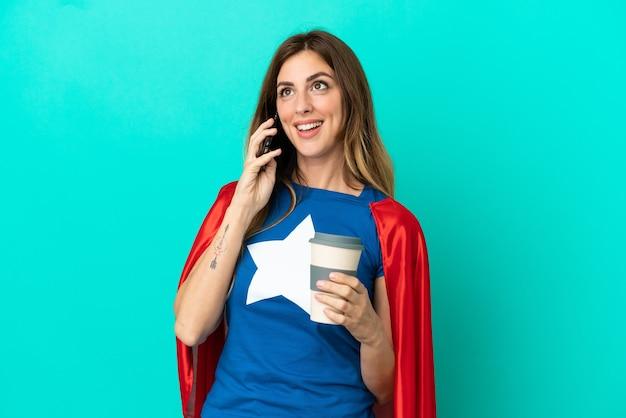 Super hero blanke vrouw geïsoleerd op blauwe achtergrond met koffie om mee te nemen en een mobiel