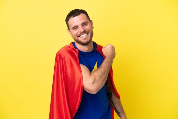 Super hero braziliaanse man geïsoleerd op gele achtergrond die een overwinning viert