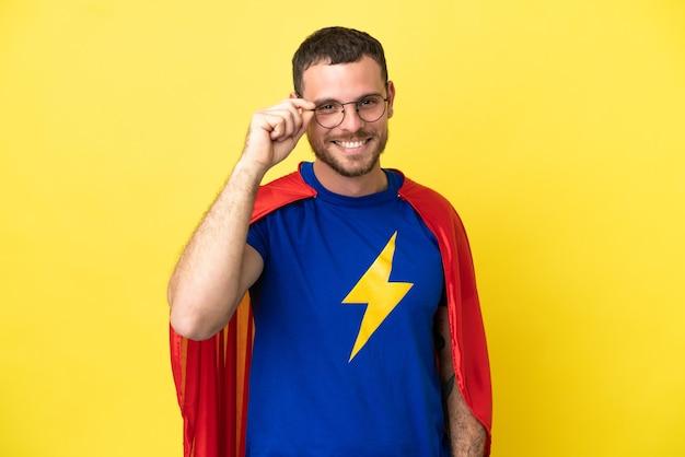 Super hero braziliaanse man geïsoleerd op gele achtergrond met bril en happy