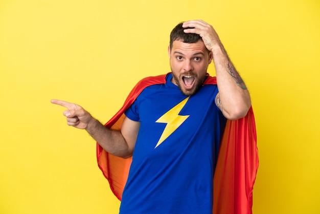 Super hero braziliaanse man geïsoleerd op gele achtergrond verrast en wijzende vinger naar de zijkant