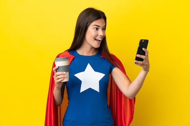 Super hero braziliaanse vrouw geïsoleerd op gele achtergrond met koffie om mee te nemen en een mobiel