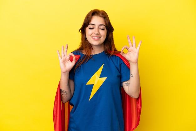 Super hero roodharige vrouw geïsoleerd op gele achtergrond in zen pose