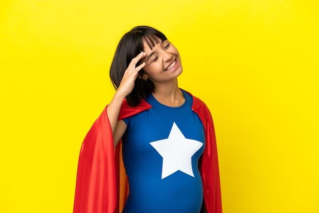 Super hero zwangere vrouw geïsoleerd op een gele achtergrond die veel lacht