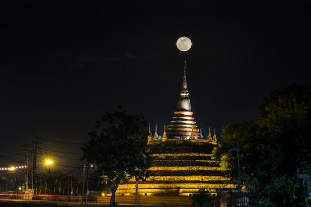 Super maan in de nachtelijke hemel en silhouet van de oude pagode wat ratchaburana