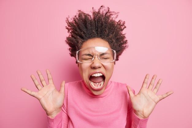 Super opgewonden emotionele afro-amerikaanse vrouw wordt gek en schreeuwt met wijd geopende mond houdt handpalmen omhoog, heeft krullend haar overeind, draagt een transparante bril en een roze trui. emoties concept