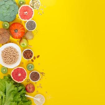 Superfoods op geel met exemplaarruimte. groenten, fruit, kruiden en zaden. gezond vegetarisch eten
