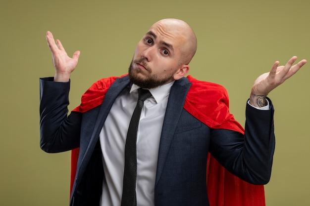 Superheld bebaarde zakenman in rode cape op zoek schouderophalend schouders wordt verward geen antwoord staande over lichtgroene muur