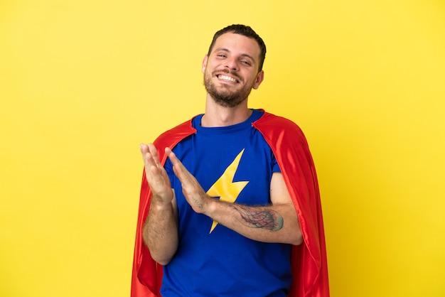 Superheld braziliaanse man geïsoleerd op gele achtergrond applaudisseren na presentatie in een conferentie