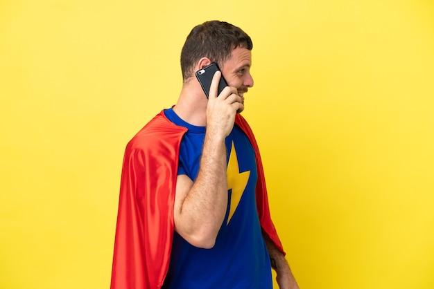 Superheld braziliaanse man geïsoleerd op gele achtergrond die een gesprek voert met de mobiele telefoon met iemand