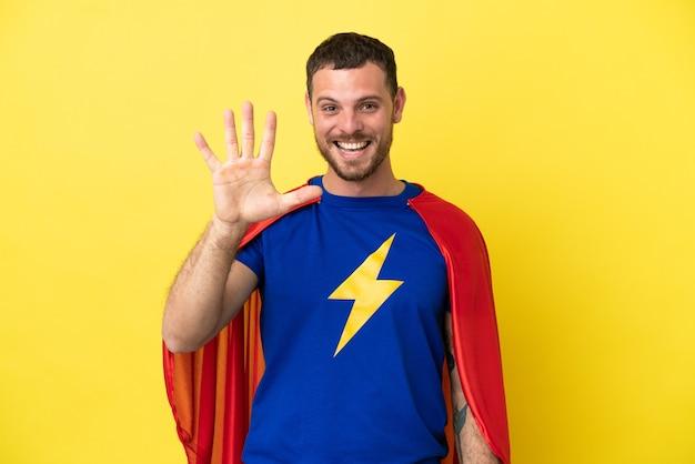 Superheld braziliaanse man geïsoleerd op gele achtergrond die vijf met vingers telt
