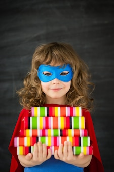 Superheld kind in de klas tegen blackboard