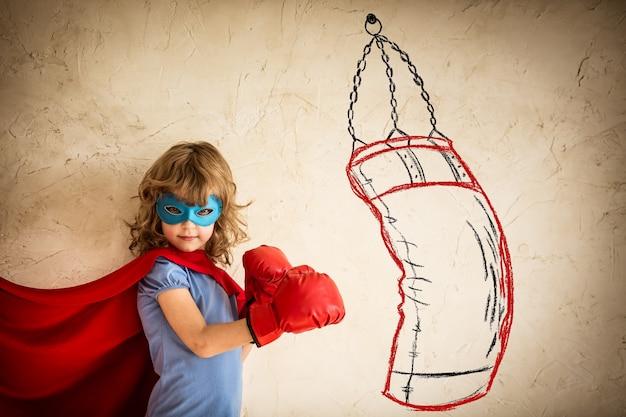 Superheld kind in rode bokshandschoenen ponsen op de getekende zak. winnaar en succesconcept