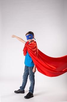 Superheld kind in rode cape wapperend op de wind