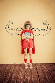 Superheld kind met getekende spieren tegen de achtergrond van de grunge muur. succes en winnaar concept