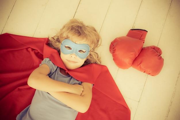 Superheld kind met rode bokshandschoenen. retro getint