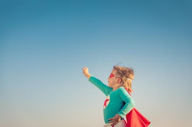 Superheld kind tegen blauwe zomer hemelachtergrond. super held jongen buiten plezier.