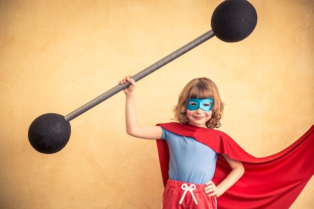 Superheld kind tegen de achtergrond van de grungemuur. kid houdt een halter vast. succes en winnaar concept