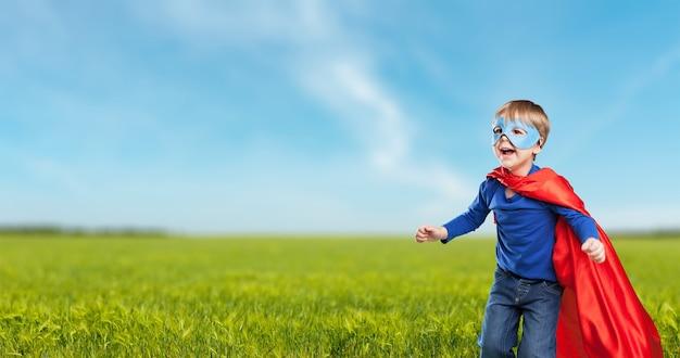 Superheld kind tegen dramatische blauwe hemelachtergrond