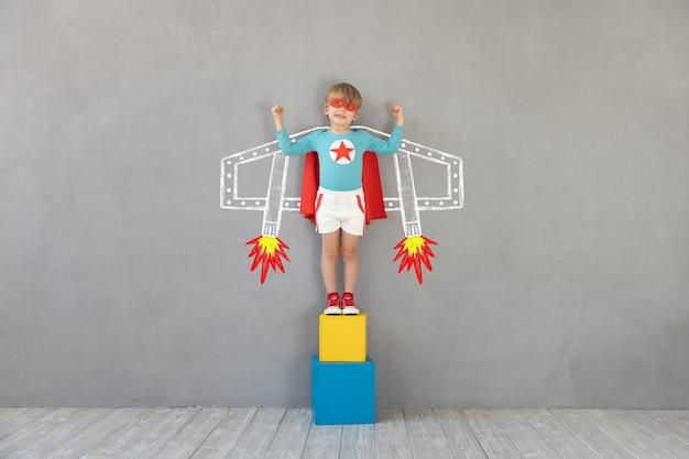Superheld kind thuis spelen. super held kind met plezier binnen. childrens droom en verbeelding concept