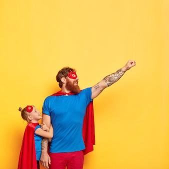 Superheld man besteedt vrije tijd met klein kind, maakt vliegende gebaar, steekt vuist op