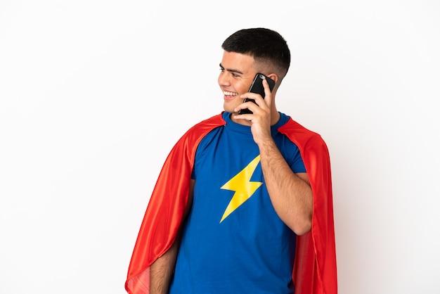 Superheld over geïsoleerde witte achtergrond die een gesprek voert met de mobiele telefoon met iemand