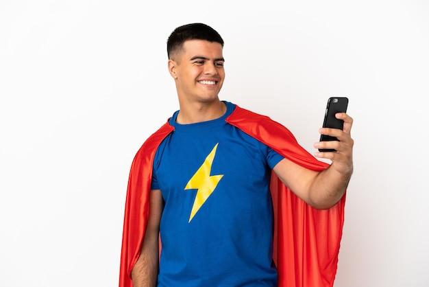 Superheld over geïsoleerde witte achtergrond die een selfie maakt