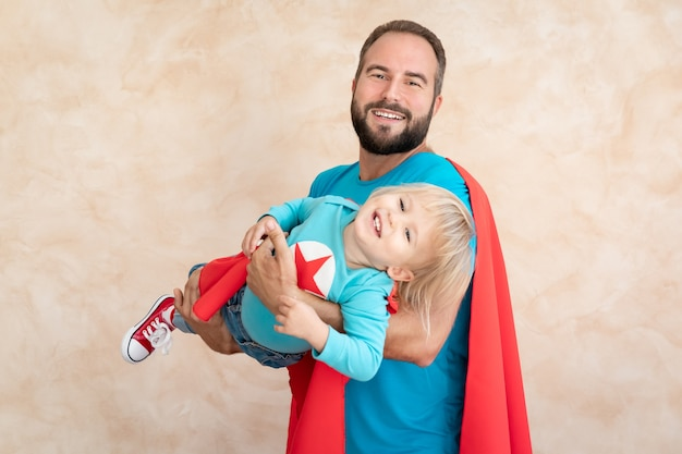 Superheld van man en kind thuis. superheld vader en zoon samen plezier.