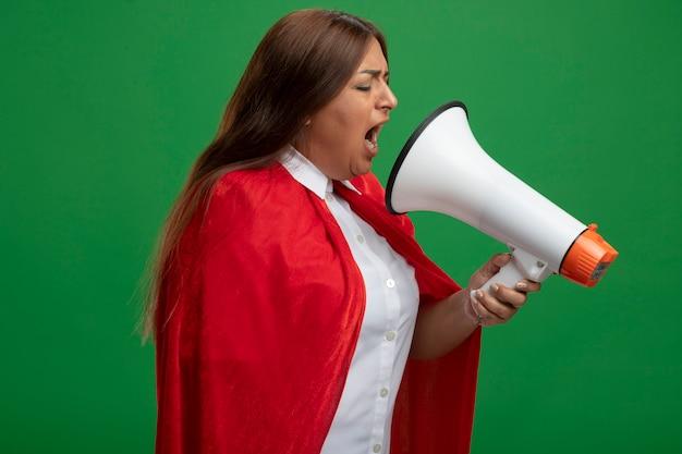 Superheld vrouw van middelbare leeftijd met gesloten ogen spreekt op luidspreker geïsoleerd op groen