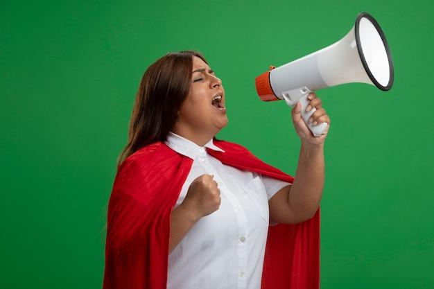 Superheld vrouw van middelbare leeftijd met gesloten ogen spreekt op luidspreker geïsoleerd op groene achtergrond
