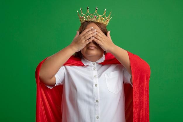 Superheld vrouw van middelbare leeftijd met kroon bedekte ogen met handen geïsoleerd op een groene achtergrond