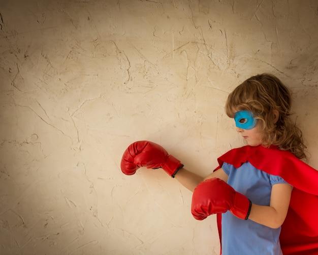 Superheldenkind gekleed in rode cape, bokshandschoenen en blauw masker tegen de achtergrond van de grungemuur
