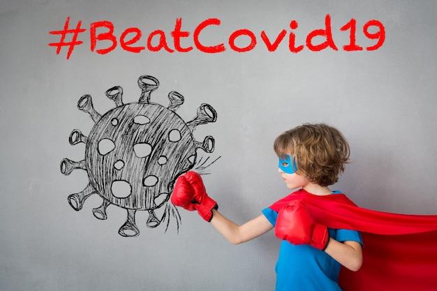 Superheldenkind versloeg covid-19. superheld jongen ponsen op het getekende coronavirus. winnaar en succesconcept