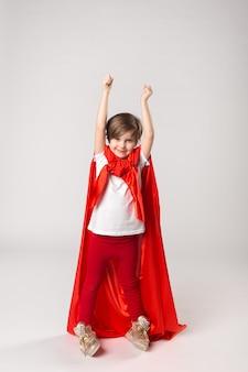 Superheldenmeisje in rode cape stak haar handen omhoog