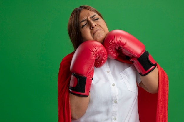 Superheldwijfje dat op middelbare leeftijd bokshandschoenen draagt - die op groene achtergrond worden geïsoleerd