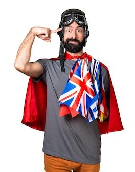 Superhero met veel vlaggen die een gek gebaar maken