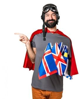 Superhero met veel vlaggen die naar de zijder wijzen