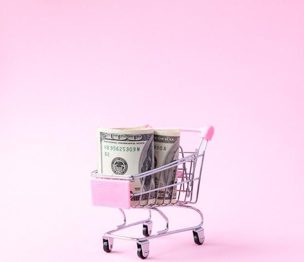 Supermarkt kar vol met bankbiljetten van de amerikaanse dollar op een roze